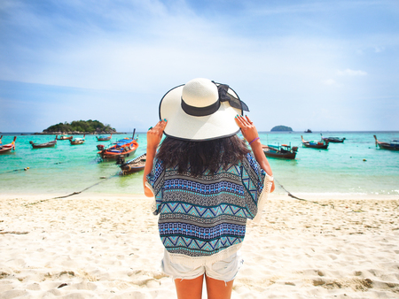 Young woman with her white straw hat on the beach and looking to the sea in sunny summer day for holiday or vacation concept,Koh Lipe island in Thailand.