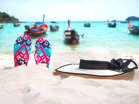 Colorful flip flops and white hat on the beach with seascape background for summer holiday concept.