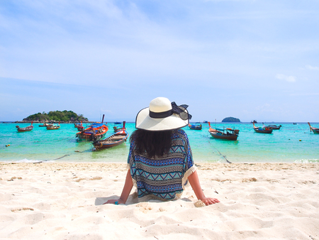 Young asian woman with her white straw hat chilling on the beach and looking to the sea in sunny summer day for holiday or vacation concept,Koh Lipe island in Thailand. Reklamní fotografie - 98806872