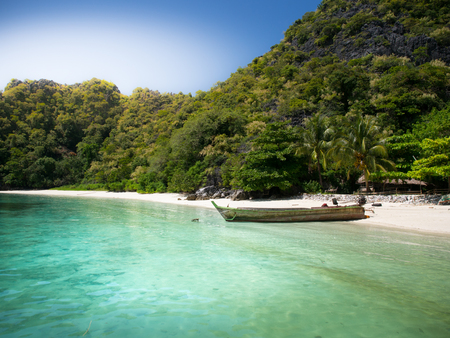 Wooden boat on white sand beach at the sea in sunny day for travel and holiday concept.