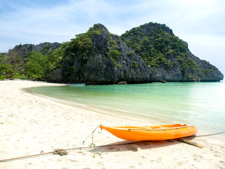 Orange kayak boat on white sand beach at the sea with mountains view background for summer holiday concept.