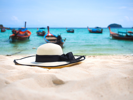white straw hat on sand beach with seascape background for summer holiday concept.