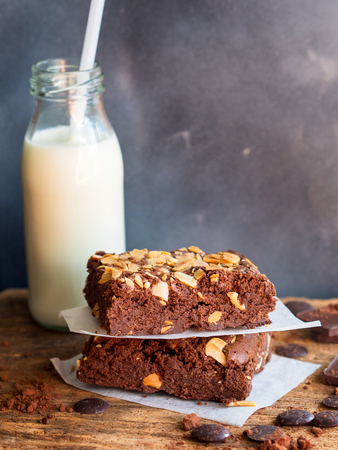 Fudge brownies dark chocolate cake topping with almond slice on wooden table with bottle of milk background for winter bakery concept.