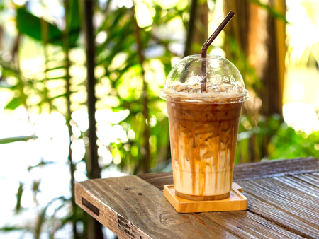 Iced caramel macchiato coffee on wooden table with natural background for summer drink concept.