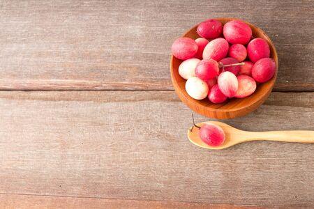 crimson colour: Carissa carandas fruits in wood bowl on wood background