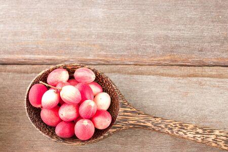 crimson colour: Carissa carandas fruits in wood spoon on wood background