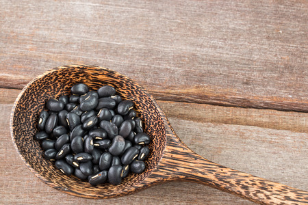black bean: Black bean in wood spoon on wood background Stock Photo