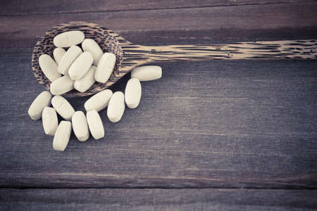 cross process: Pills on spoon on wood background cross process vintage style