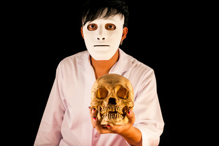 The man in white mask holding skull in hand on black background