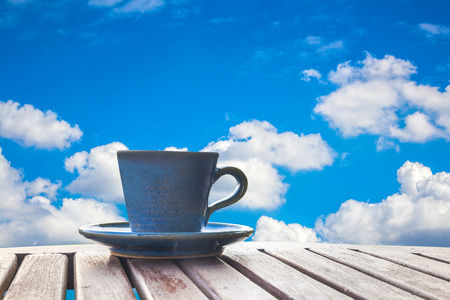 coffee cup on wood table with blue sky background