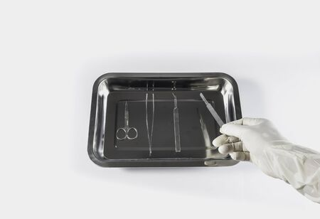 surgery tools: Surgery tools in tray with hand in rubber glove white background