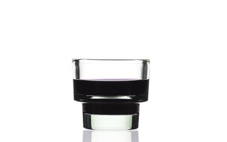 dark purple: Dark purple water in glass with reflection on white background