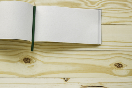 Open book with pencil on wood background