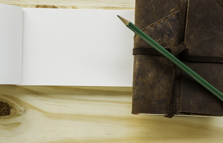 Old leather book with pencil on wood background