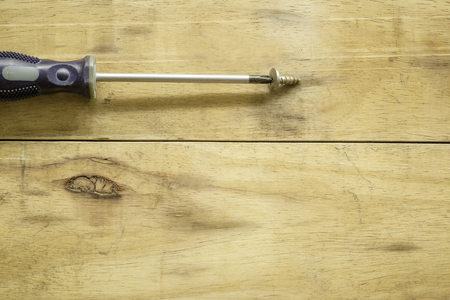 Screwdriver on bolts with wood background