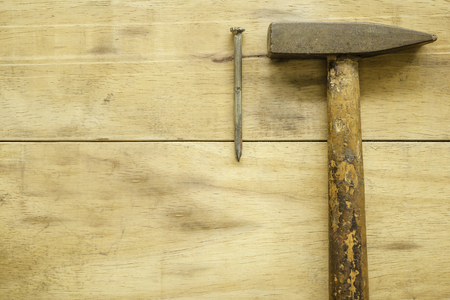 Hammer and nail on wood background