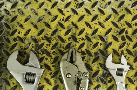 Adjustable wrench and locking plier on yellow dirty metal plate background texture