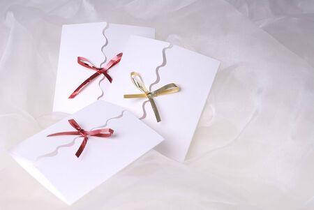 drie witte handgemaakte uitnodiging op witte zijde achtergrond Stockfoto