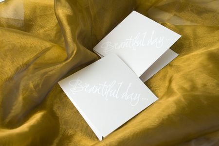 two white handmade invitation on gold silk background