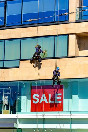 two industrial window cleaners on tall building Stock Photo