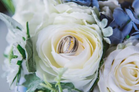 wedding rings and flowers and branches close up before the ceremony