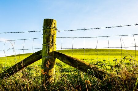 Fence line, the typical wood post and barbed wire barrier UK
