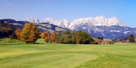Panoramic view of grassland and mountains on a sunny day at Kitzbuhel - Austria