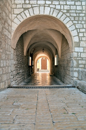 krk: Stone arc passage at Krk Cathedral in old center in Krk - Croatia Stock Photo