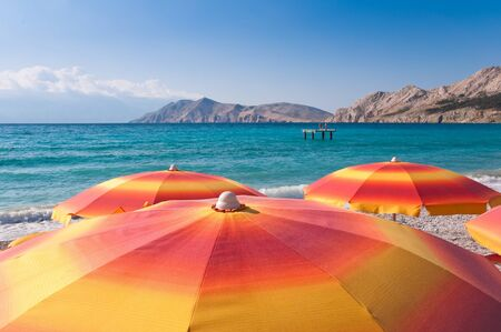 Orange Sunshades on beach at baska - Krk - Croatia photo
