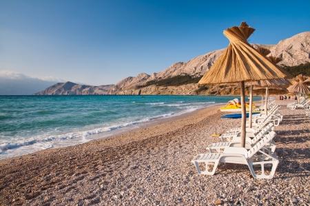 Sunshade and deck chair on beach at Baska in Krk - Croatia Stock Photo - 16901582