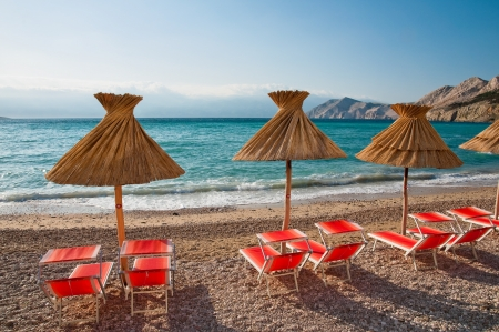 Three sunshades and orange deck chairs on beach at Baska - Krk - Croatia Stock Photo - 16901577
