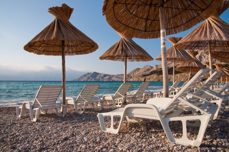 Deck chairs and sunshade on beach at Baska - Krk - Croatia Stock Photo - 17194608