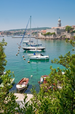 sailingboat: Boats on little port beside Krk old town view with vegetation - Croatia