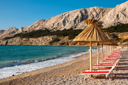 Sunshades and orange deck chairs on beach at Baska - Krk - Croatia Stock Photo - 17216030