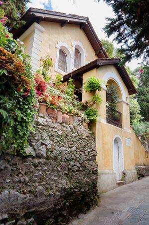 CAPRI, ITALY - SEPTEMBER 11, 2014:  Yellow house in beautiful street of Capri, Italy Editorial