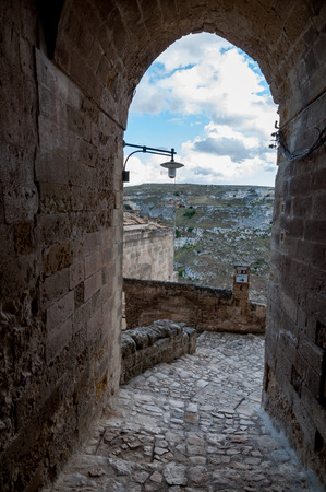 rupestrian: Passage with lantern leading to view of ancient caverns of Sassi di Matera - Italy Editorial