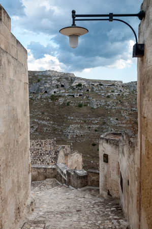 Passage with lantern leading to view of ancient caverns of Sassi di Matera - Italy Editorial