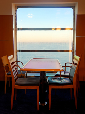 unoccupied: Unoccupied chairs and a table by the window on the ferry during sunrise.