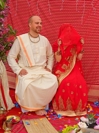 BUSHEY, JUNE 19: Hindu wedding in the Vedic tradition, England, UK 2016.  The bride has hidden her face with a sari before the marriage ceremony.