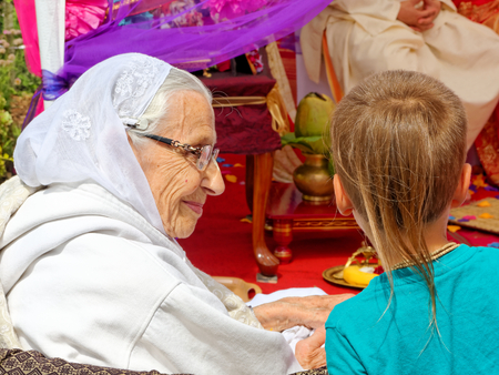 hair tuft: BUSHEY, JUNE 19: Hindu wedding in the Vedic tradition, England, UK 2016.  Old woman talking to the boy with the characteristic of Krishna devotees, tuft of hair on the head.