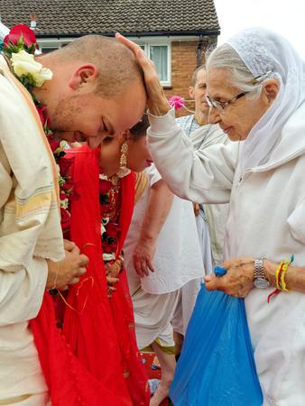 exalt: BUSHEY, JUNE 19: Hindu wedding in the Vedic tradition, England, UK 2016.  Elderly woman devotee of Krishna bless a bride and a bridegroom.
