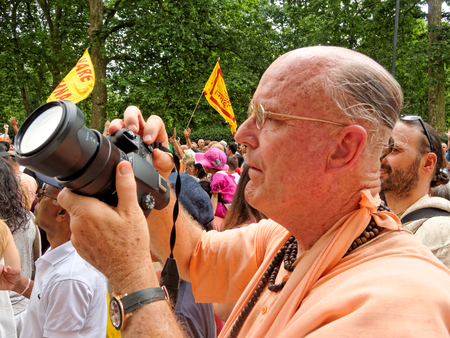 reportage: LONDON - JUNE 18: The cart festival called Rathayatra in London June 18, 2017. The monk in the renounced order of life with the camera makes a photo reportage of a colorful festival.