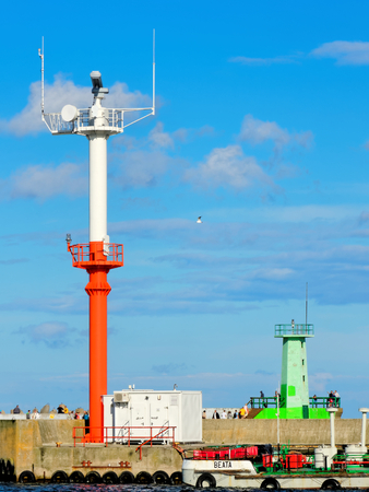 Radar tower and lighthouse at the entrance to the sea port. Stock Photo