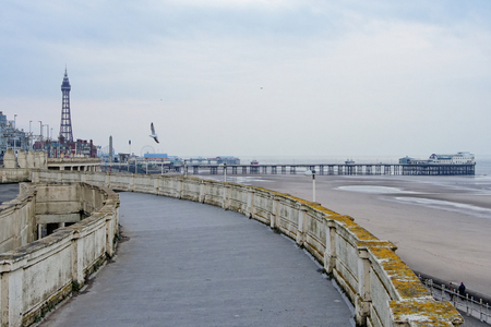 Winter view of the Blackpool coast with promenade, pier and a tower.