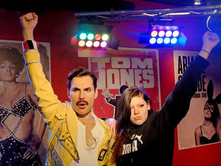 BLACKPOOL, JANUARY 14: Madame Tussauds, UK 2018. Wax statue of Freddie Mercury, best known as the lead vocalist of the rock band Queen and a posing girl, both with raised hands. Redakční