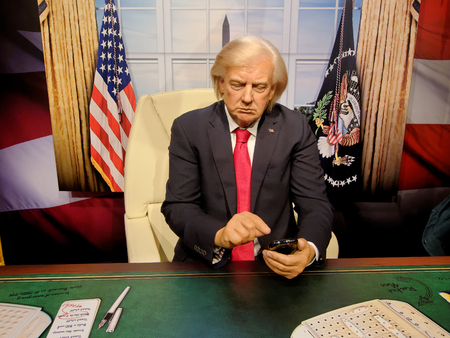 BLACKPOOL, JANUARY 14: Madame Tussauds, UK 2018. Wax figure of Donald Trump pointing to a cell phone, President in White House.