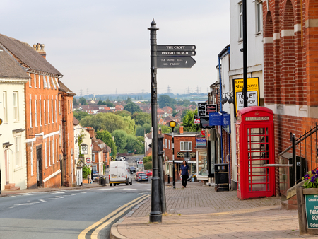 COLESHILL, AUGUST 06: Signpost and red telephone booth on High Street, UK, 2018.