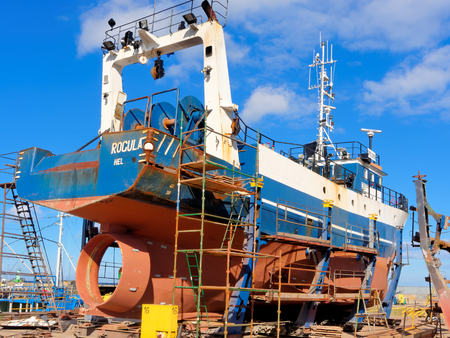 Fishing boat in dry dock under repair.