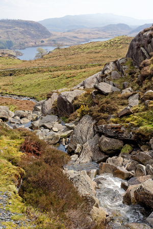 View of the valley from a flowing stream on the Cwmorthin Waterfall trail in the mountains of Snowdonia National Park, Wales.
