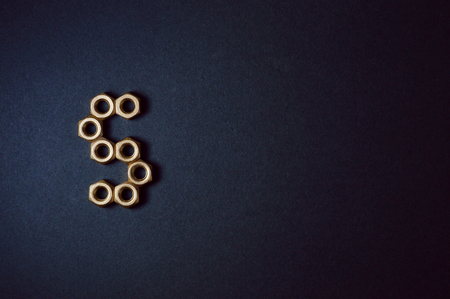 Golden mechanic nuts forming shapes and numbers in dark background. 版權商用圖片